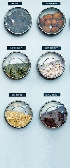 Små burkar av plåt med glas av lock fyllda med kryddor