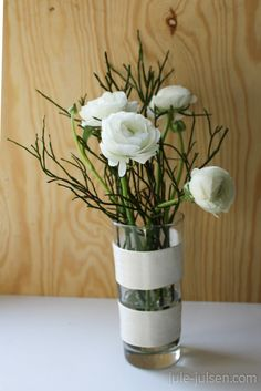 ranunculus in water glass wrapped with white ribbon