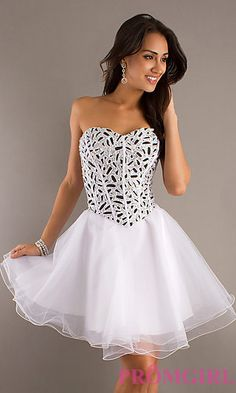 Go for a classic prom dress style with an updated design in this sensational short ball gown. A sexy strapless corset style bodice flatters your figure and sparkling accents add a magical touch. The short A-line skirt is full and features a sheer overlay. A short strapless corset dress for prom in black and white.