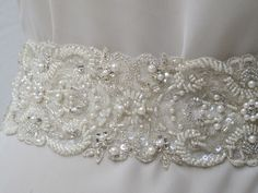 Beaded Bridal Sash.  Pearls, crystal beads, sequins on satin ribbon.  More pearl, less rhinestone bling.  Sophisticated.