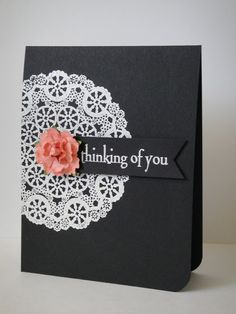 handmade card ... clean and simple ... black base card ... one rounded corner ... white embossed doily ... punch of color from a small coral-colored dimensional flower ..