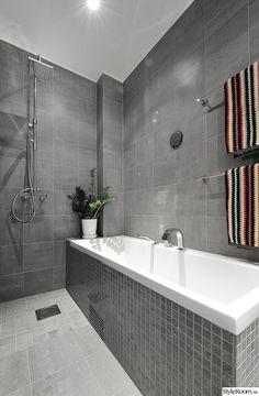 Light grey tile floor, darker grey tile walls