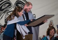 The royal couple look at a painted First Nations logo they were presented with...
