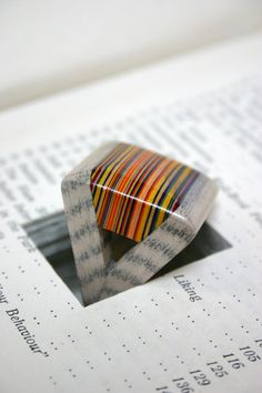 """Jeremy May has captured the beauty of paper via a unique laminating process. Littlefly paper jewellery is made by laminating hundreds sheets of paper together, then carefully finishing to a high gloss. The paper is selected and carefully removed from a book, and the jewellery re-inserted in the excavated space."