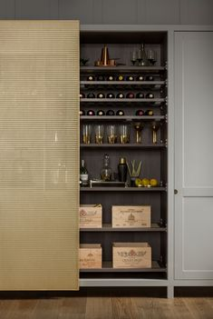Behind the sliding brass mesh door is a wine section detailed with Lanserring's sawtooth shelf supports. It has bottle racks, leather-topped glassware shelves, and brass-mesh-inset shelves for ventilation.