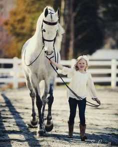 Little girl leading a gorgeous white horse with black markings.