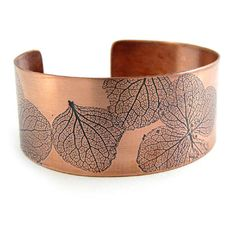 Natural Impressions Copper Cuff Bracelet. Embellished with the impression of actual plants, this artisan-made copper cuff permanently captures the organic lines of nature in metal. A dark patina highlights the details, while the copper base reinforces the natural character. Due to use of actual leaves, each is a one-of-a-kind creation and will vary slightly.