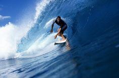 SURFER RIDING PERFECT BLUE WAVE NEAR TAHITI