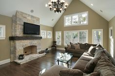 Family room style with hard wood floor, large sectional sofa, television mounted above brick fireplace with white cathedral ceilings against beige colored walls
