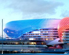Yas Hotel – Abu Dhabi    This 36 billion dollar hotel's main feature is the color-changing, sweeping, curvilinear forms that sit atop the hotel towers. The curvilinear forms are comprised of nearly 6,000 pivoting diamond-shaped glass panels. See http://www.mediaarchitecture.org/page/9/