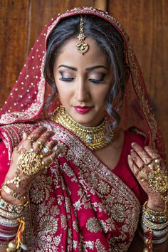 The simply stunning bride in her red sari - Photo by Joy Marie Studios