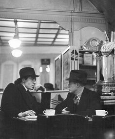 Wolf Suschitzky: These little cafés do not exist any more.Typical for the time are the men wearing hats, also the big urn with hot water for making tea.