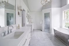 White and gray bathroom features a corner shower clad in gray marble tiles finished with a seamless glass door next to a Freestanding cast iron tub placed under windows.