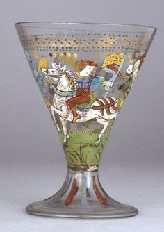 Goblet; glass; conical bowl extending into folded bell-shaped pad-base; enamelled in colours with mounted knight with banner; man standing with ewer and large arrow; intertwined floral scroll; band of gold imbrications and blue and green dots; blue and red vertical stripes on foot. Italy (Venice), late 15th century.