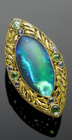 An Antique Black Opal, Demantoid Garnet and Sapphire Ring, Lightning Ridge, New South Wales, Australia, Circa 1905. The black opal, of marquise-shaped outline, estimated to weigh approximately 16 carats, having a pseudo effect of a cat's eye phenomenon with vivid broad flash of green and electric blue in a zig-zag pattern. Set into a yellow gold mount with foliate motif decoration accented with four circular-cut Russian demantoid garnets and six small sapphires. Inscribed with maker's mark…
