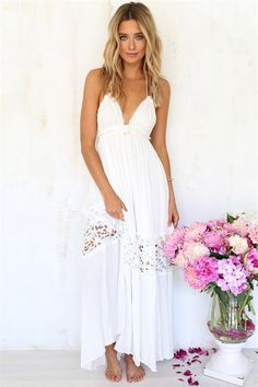 The Ever After Dress is a floor length halter neck maxi in cream crepe type fabric with adjustable rope ties for back neck and under bust with gold mini bell detailing. Lining till the end of first skirt panel, open cut crochet detail panel on skirt, raw edge bust cups, regular fit. By Sabo Skirt.