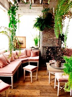 Rustic living room with lots of hanging plants and pink sofa bench
