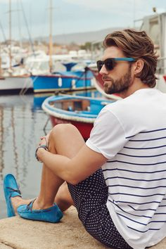 The style of the summer, wear a printed pair of shorts, a stripe oversize t-shirt and colored loafers which match to the glasses.