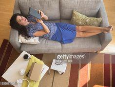 Stockfoto : Mixed race woman using digital tablet on sofa