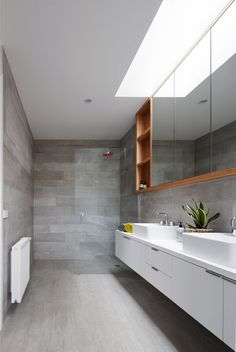 Simple palette is enhanced by a beautiful skylight in this bathroom at 700 Haus a Modern Farmhouse by Glow Building Design (via Lunchbox Architect). Also love the Caroma Marc Newson showerhead! Warm Bathroom, Bathroom Renos, Skylight Bathroom, Bathroom Ideas, Concrete Bathroom, Washroom, Bathroom Remodeling, Bathroom Faucets, Bad Inspiration