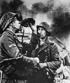 Two german Waffen SS soldiers have a break. In the background there is a destroyed T-34 tank. The soldiers are from the 3rd SS Panzer Division Totenkopf.