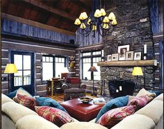 Warm and inviting family room in the square log, reclaimed barnwood, and stacked stone fireplace.  Hamilton, Montana