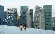 Ein Bad der Extraklasse genießen die beiden Touristen im Marina Bay Hotel in Singapur. Der Dachgarten des Fünf-Sterne-Hotels mit seinem großen Pool bietet einen atemberaubenden Blick über die Stadt und das Meer.