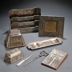 Six-piece Tiffany Studios Chinese Pattern Desk Set, Patinated bronze, New York, 1897-1918, Comprised of a four-tier letter holder, no. 1756; large inkwell, no. 1753; stamp box, no. 754; pen tray, no. 1755; note pad; and picture frame, no. 1757; all in silvered bronze, finish wear, all marked Tiffany Studios New York and numbered; accompanied by an unrelated pair of German Art Deco scissors and a ribbed-handle letter holder, unmarked, Tiffany pieces ht. 8 1/8 to 2 3/8 in.