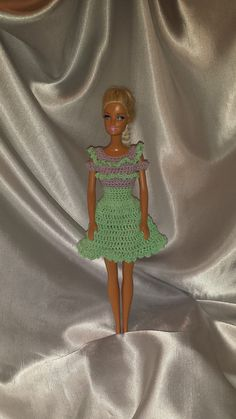 Barbie will be ready for a stroll along the boardwalk in this beautiful hand crocheted dress with open shoulders. This dress is a mint green accented with a purple neckline/bodice using cotton crochet thread. There are snaps to ensure that Barbie stays dressed. This outfit will suit both vintage and modern Barbie and Fashion Doll shapes. Dress only - doll, shoes and props not included. This item was made with cotton and will shrink. Wash cold water only and air dry. Item may need to be…