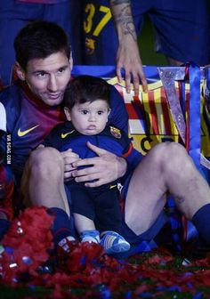 Messi and his son Thiago.  Wow, somebody has cubby cheeks