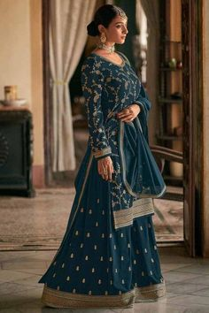 Exuding elegance and finished with perfection, this prussian blue georgette sharara suit which exudes feminine charm. This u neck and full sleeve party wear attire prettified with zari, stone, and sequins work. Present with georgette sharara pants in prussian blue color with prussian blue georgette dupatta. Sharara pants and dupatta embroidered with stone and zari work. #shararasuits #malaysia #Indianwear #weddingwear #andaazfashion Indian Attire, Indian Wear, Sharara Suit, Salwar Kameez, Pantalon Cigarette, Bollywood Dress, Blue Bridesmaids, Costume, Indian Dresses