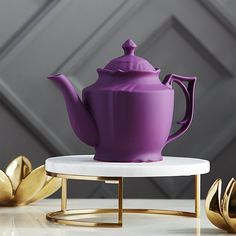 Shop lizzy royal purple teapot.   We couldn't resist a loving nod to the Queen herself.  (Lizzy, AKA Queen Elizabeth. ) More cool than prim and proper, Victorian-style teapot pours modern in a chic coat of purple silicone over porcelain.