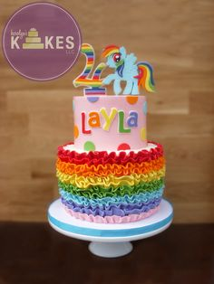 My Little Pony KAKE! This cake is a variation of one of my previous designs :) Cake is iced in buttercream.  Marshmallow Fondant ruffles, #4 and Rainbow Dash Pony.