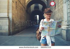 Happy female tourist with backpack on shoulders exploring map while standing in alley near vintage building, trendy woman traveler with smile reading geographical atlas while touring in old city