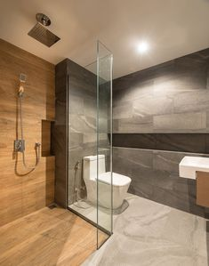 This modern bathroom uses a mixture of grey tiles, wood, and glass, to create a calm experience. Grey Bathroom Tiles, Grey Bathrooms, Bathroom Layout, Grey Tiles, Bathroom Ideas, Shower Tiles, Bathroom Furniture, Wood Tiles, Bathroom Vanities