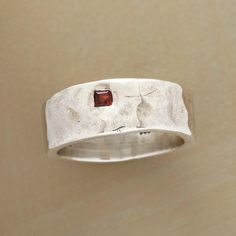 GARNET GALLERY RING -- A hammered square setting in a sterling silver band surrounds the bright light of a single red garnet. Handcrafted for Sundance. Whole sizes 5 to 9.
