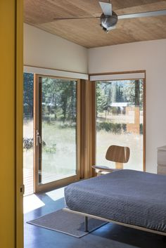 The bedroom opens out onto the deck and meadow beyond. Photo 5 of Lot 6 modern home