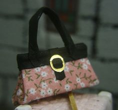 Handmade miniature handbag. Pink floral material with black leather trim and handles.