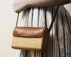 The oak bag by Haydanhuya is handmade using one piece of oak wood and vegetable tanned leather. The bag is 6.8 inches wide, 2 inches deep, and 4 inches tall.