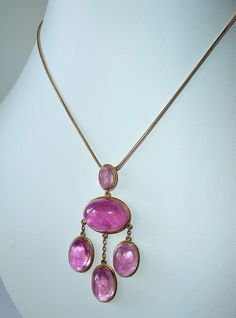 A stunning vintage rubellite tourmaline pendant beautifully made in 14k yellow gold. The magnificent pendant features five fabulous pink tourmaline