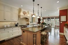 Large kitchen with white cabinets and natural wood island with dark countertops. Splash of color with one red wall.