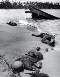 Three American soldiers lie half-buried in the sand at Buna Beach on New Guinea. This photo was taken in February 1943, but not published un...