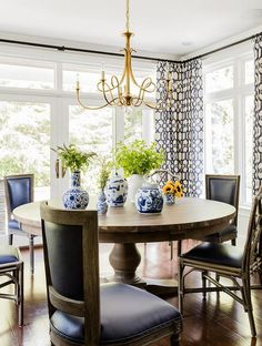 Chic dining room features a Eric Cohler Double Twist Large Chandelier illuminating a large round wood dining table lined with French black leather dining chairs surrounded by windows dressed in ivory and black print curtains.