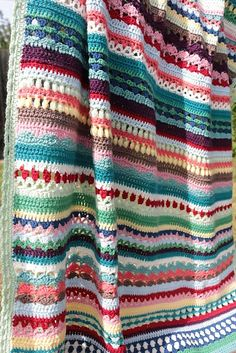 This crochet afghan is colorful, happy and designed with lots of artistic attention for details. This project is so ideal for a stash-down