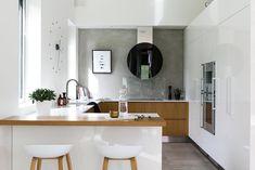 Tyylikäs moderni keittiö, jossa puuta ja korkeakiiltoisia valkoisia kaappeja. Saarekkeen ääreltä löytyy tyyliin täydellisesti sopivat Hay About a Stool baarijakkarat.