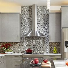 The new glass mosaic backsplash echoes the colours of the cabinets