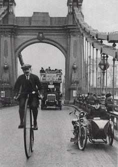 A cyclist riding a penny farthing over Hammersmith Bridge, London, 1900
