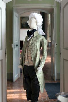 """Redingote en taffetas pékiné ombré de rayures gris vert mauve rouge or et noir, avec des boutons en pareil, gilet droit en satin crème brodé de soie polychrome, médaillons, semis de fleurs et brindilles. La redingote est portée sur une culotte en satin tête de nègre. La carvate est dit """"solitaire"""". 1785-1790 Rococo Fashion, Men's Fashion, Fashion Outfits, Historical Costume, Historical Clothing, October Outfits, Century Textiles, Vintage Outfits, Carnival"""