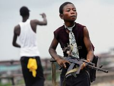 MONROVIA, LIBERIA -­ JULY 30, 2003: A child Liberian militia soldier loyal to the government walks away from firing while another taunts the...