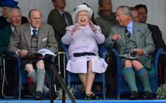 Prince Philip, the Queen  and Prince Charles cheer as competitors participate in a sack race at the Braemar Gathering in Braemar, Scotland